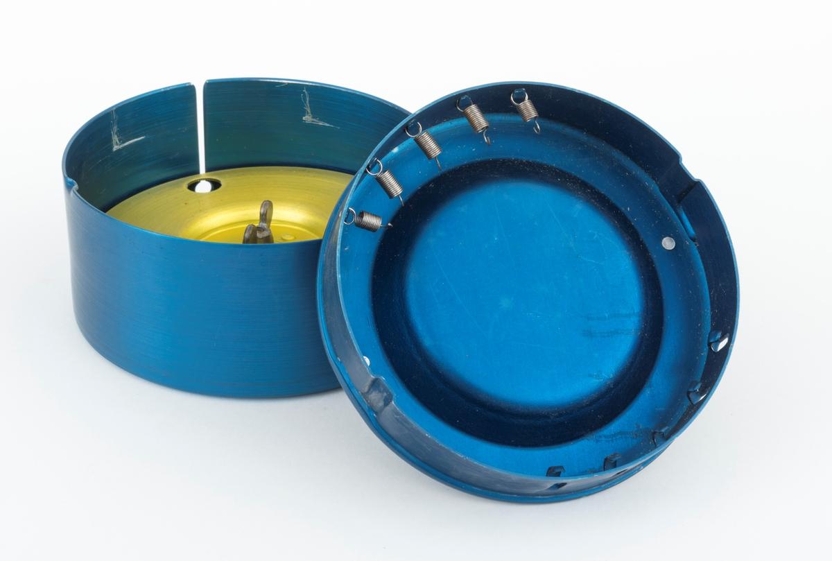 """Fiskeredskap, den såkalte «snelleboksen». Gjenstanden består av snelleboks medfølgende pappeske og bruksanvisning (se arkivreferanse og referanse til filer). Boksen er lagd av eloksert, blåfarget aluminium. Den har en utvendig diameter på 11,4 centimeter og en høyde på 5,1 centimeter. I sideveggen er det ei 4,1 centimeter djup og 2 millimeter bred spalte for fiskesena. Sentralt i botnen av boksen er det en gjenget skrue, som fungerer som omdreiingsakse for en gullfarget aluminiumsspole (snelle) med 10,7 centimeters diameter. På undersida av denne spolen er det ei messingfjær, og på oversida er den festet ved hjelp av en vingemutter. Til boksen hører det et lokk, lagd i samme materiale og med samme blåfarge. Lokket presses ned i boksen, og etter en liten vridning sitter det fastlåst. Diagonalt over en forsenkning på oversida av boksen er det påklinket et handtak med teksten «SNELLEBOKSEN  NORSK PAT. KRAV NR. 105236» i opphøyet relieff. I forsenkningen under det nevnte håndtaket finner vi teksten «FOR KASTESLUK OG SNØREFISKE """"Standard""""  KM  MADE IN NORWAY». På innsida er det festet fem små spiralfjærer på den ene sida, og det er fem kroker på den andre - for feste av sluker.  Produsentens navn og adresse, «KUNST & METALLINDUSTRI  A/S TRONDHEIM  NORGE», er innstemplet på undersida av boksen.   Snelleboksen ble overlevert til Norsk skogmuseum i en liten pappeske (12 X 12 centimeter bred, 6,5 centimeter høy), merket «15,-», antakelig en gammel pris, på undersida. I pappesken lå det også en liten trykksak, men en slags bruksanvisning med følgende tekst:  «SNELLEBOKSEN  NORSK PAT. NR. 80928  ALLE TIDERS ...  Turgjengerens ØNSKEDRØM  SNELLEBOKSEN - lages av solid aluminium, eloxert i farger. Snellen er for oppbevaring av snøret. Den roterer om en messingaksling og holdes fast med ren messingvingemutter. - Den lages i to størrelser: Standard, som måler 5 X 11 cm, har en anordning i lokket for oppsett av 5 sluker. Junior måler 5X9,5 cm. og er beregnet på å bæres i lomma. - Nå"""
