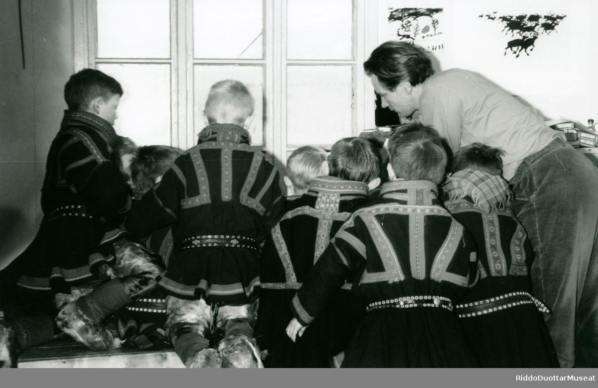 Lunttat beavddi birra oahpaheddjiin.  Skolegutter rundt bordet med læreren.