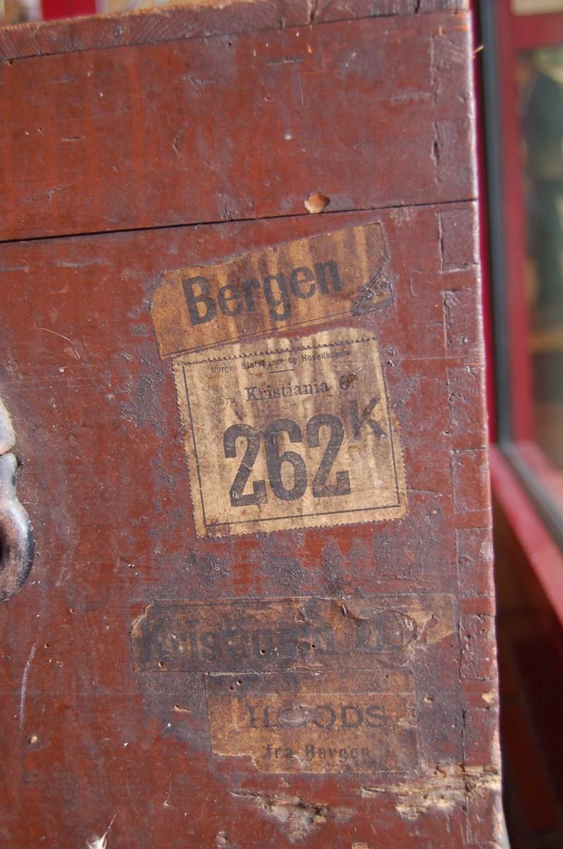 Slitt, brunmalt trekiste med hengslet lokk, bærehåndtak og lås/ nøkkelhullbeslag.