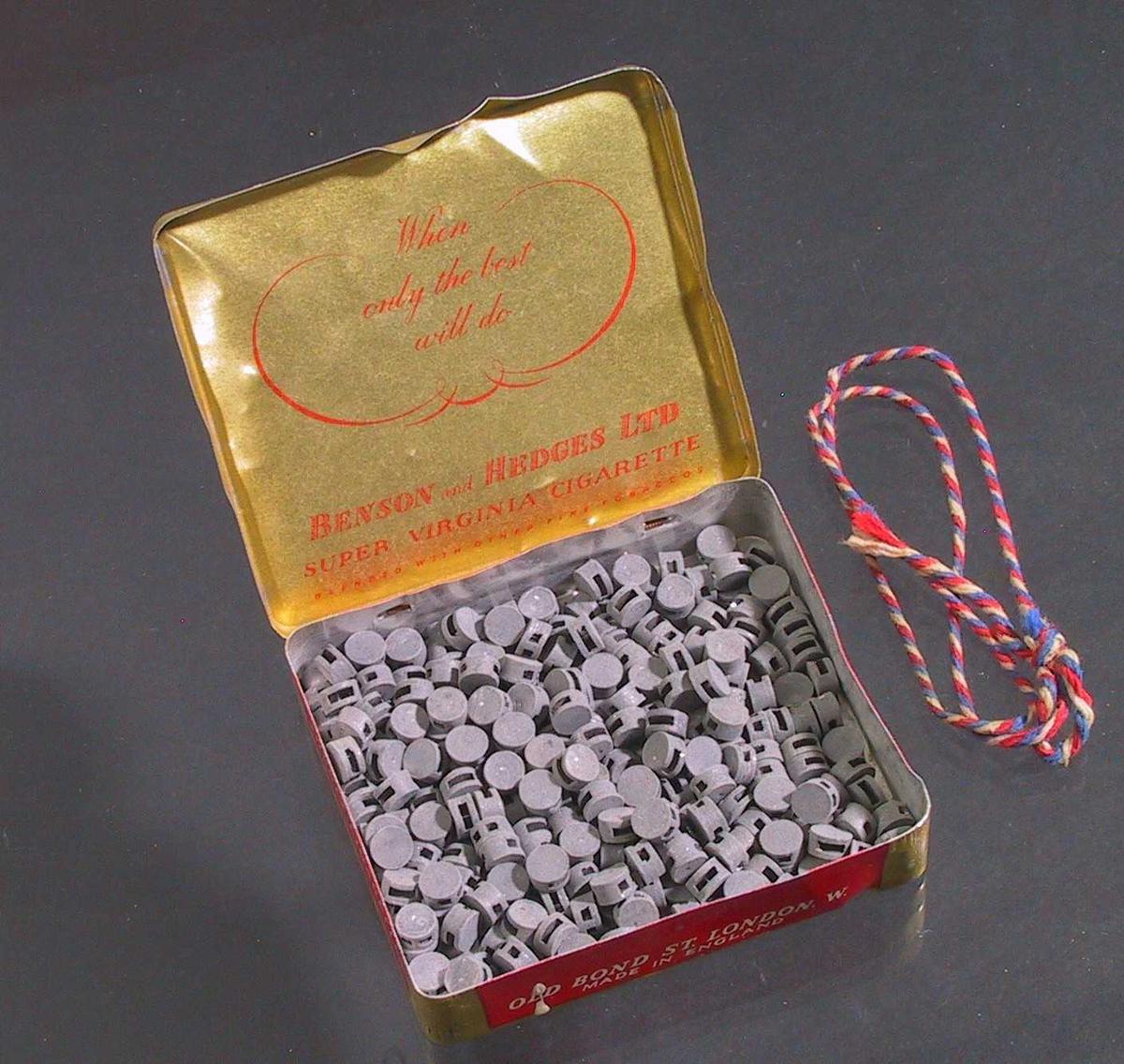 """Tollplomber av bly, ligger i rød- og gullfarget sigaretteske """"BENSON and HEDGE"""". Brukt sammen med tang av typen AAM.30621."""