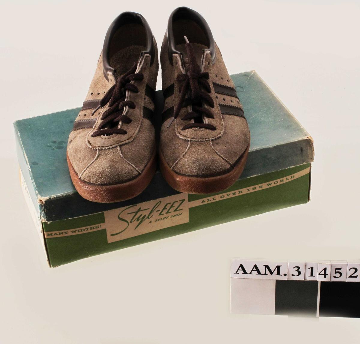 Brune joggesko, skoeske og skopose.  Skoene hører ikke sammen med eske og pose, men skoene kom inn i denne eska.  a) Lysebrune semskede joggesko med to mørkebrune skai striper, kant i mørkebrun skai og mørkebrune lisser.  Størresle 38.  Innlegg i hælen i venstre sko.  Pent brukt, men slitte såler.  b) Skoeske med lokk.  Grønn og ecru-farget eske og grønt lokk.  c)  Pose