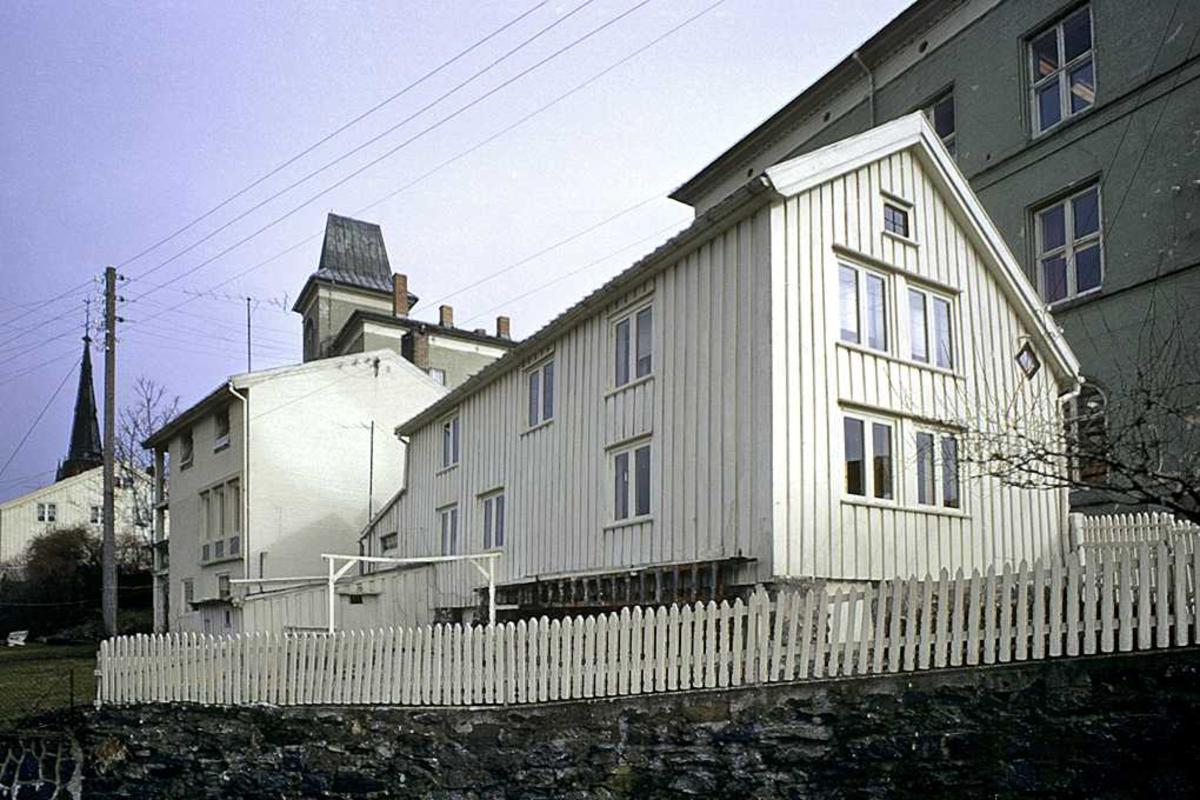 Øvre Tyholmsvei mars 74 .  Gateparti, langside av bolighus, kirketårn og skolebygning skimtes bak.