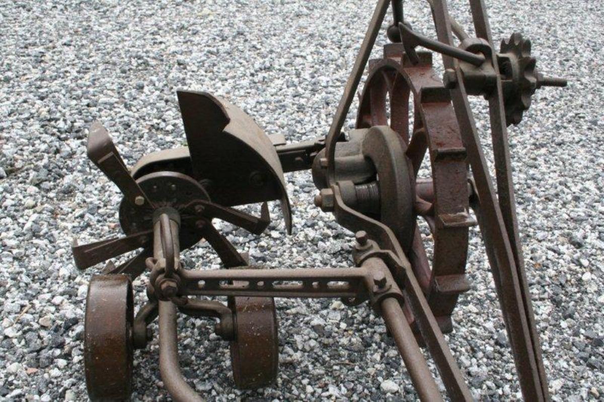 Smijernsramme med et lite hjul foran og et stort hjul bak. Kjedeoverføring til uttynningshjulet. To små bærehjul.