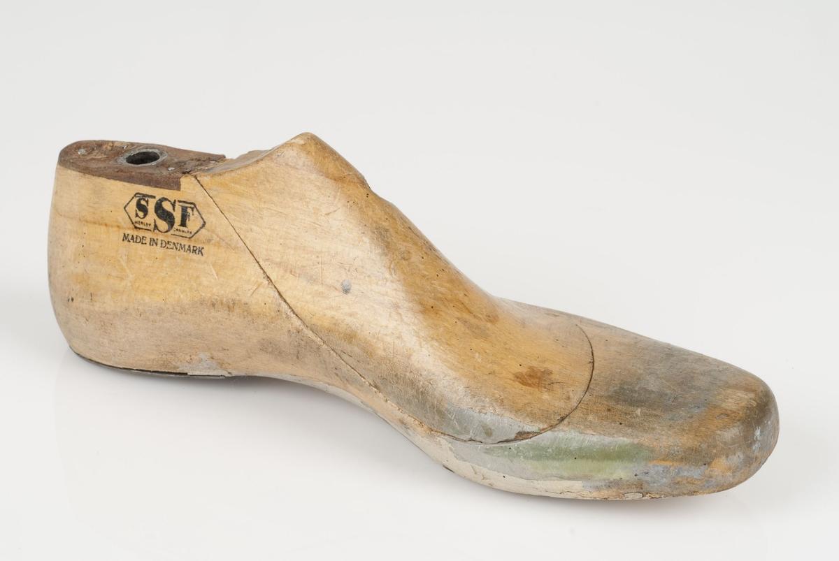 En tremodell i to deler; lest og opplest/overlest (kile). Venstrefot i skostørrelse 41, og 8 cm i vidde. Hælstykket i metall.