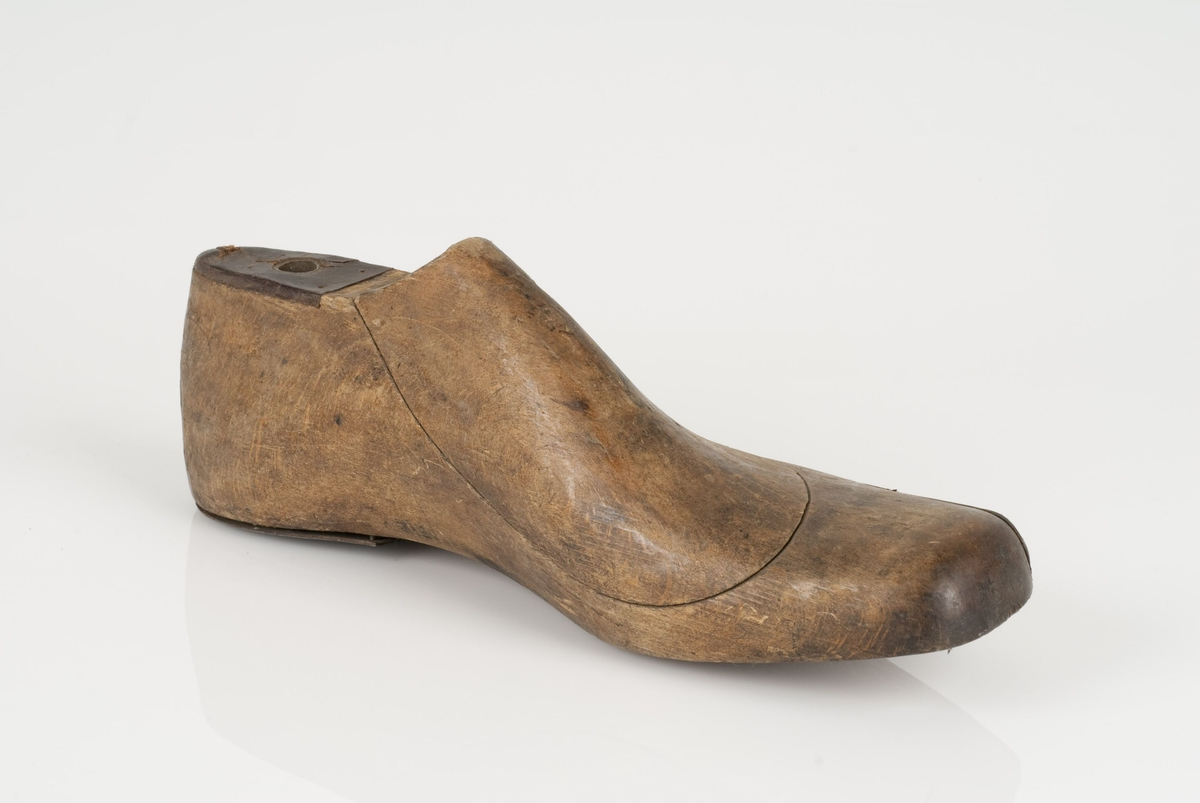 En tremodell i to deler; lest og opplest/overlest (kile). Venstrefot i skostørrelse 46, og 10 cm i vidde. Hælstykket i metall. Lestekam i skinn.