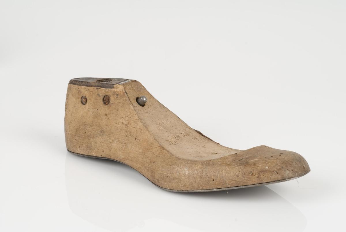 En tremodell; lest som mangler overlest. Høyrefot i skostørrelse 33 med 8 cm i vidde. Såle av metall. Lestekam av skinn.