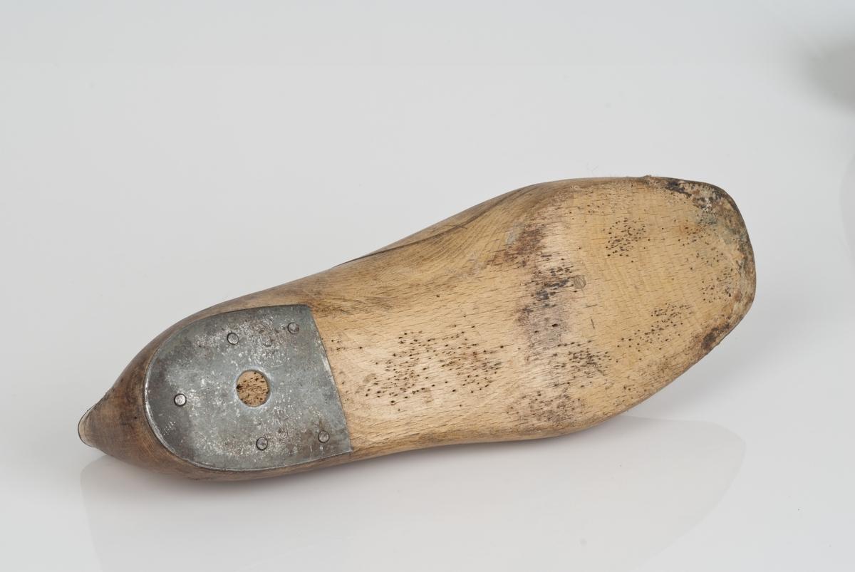 Tremodell i to deler; lest og overlest. Venstrefot i skostørrelse 39 med 9 cm i vidde. Lestekam av skinn. Hælstykket av metall.