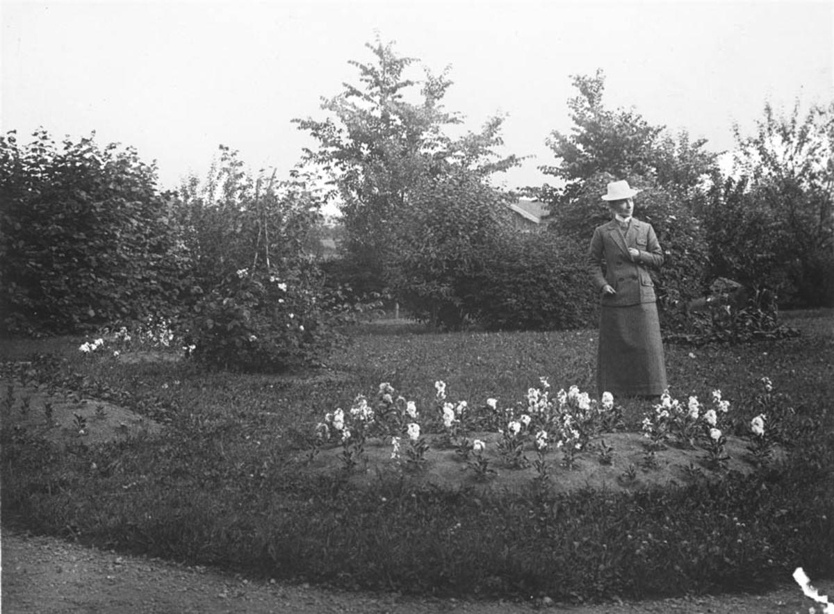 Olga Næristorp mellom blomsterbedene i haven på Vanaheim.