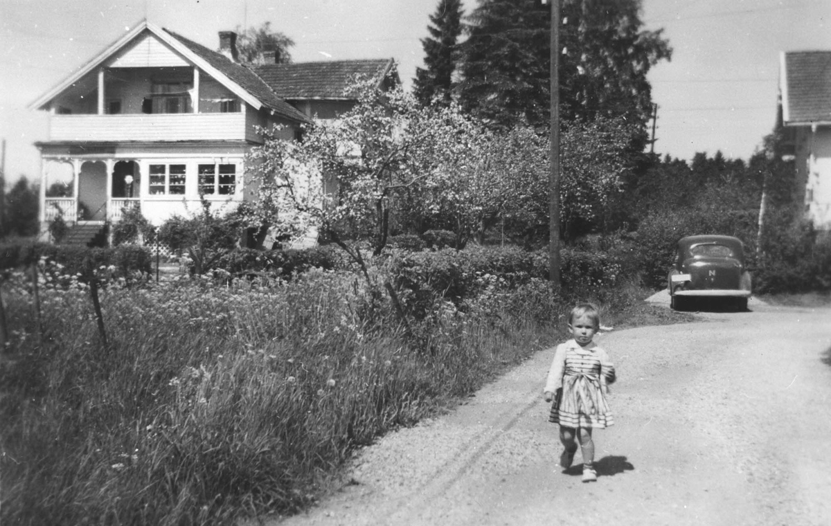Aasvang eller Bråthe gården, bygget i begynnelsen av 1900 århundre. Bente Gundersen, tre år gammel, på vegen ved huset. Bil i bakgrunnen.