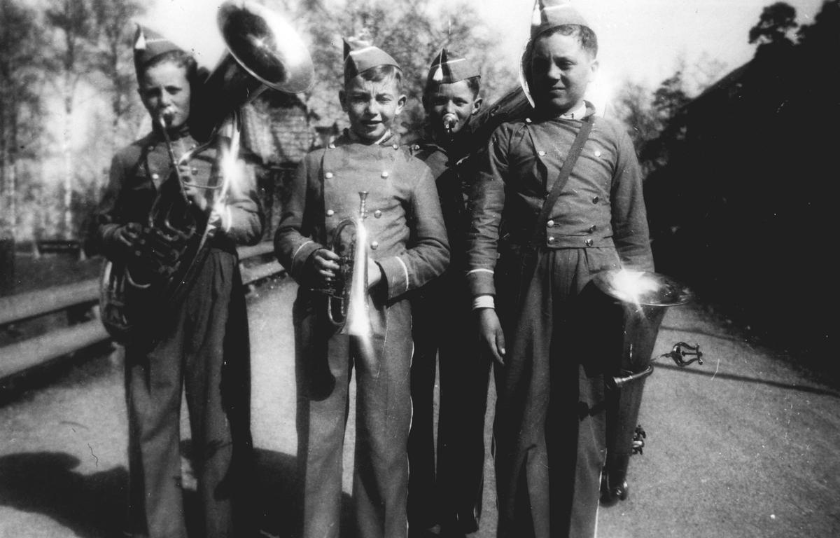 Fire uniformerte skolemusikanter m/instrumenter. Oppegård guttemusikk.