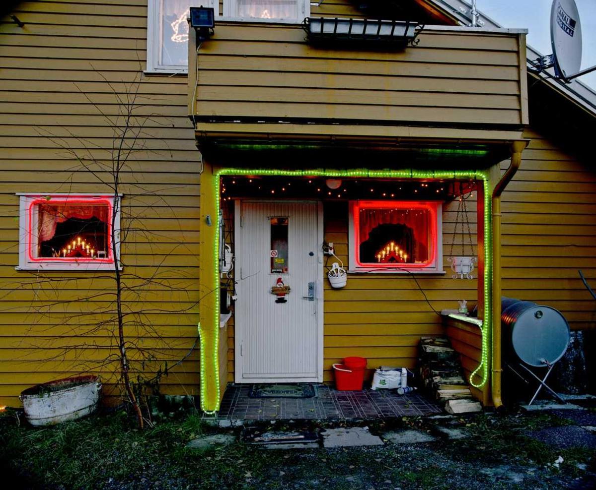 Julebelysning.  Fantastisk julebelysning på enebolig. Røde lysslanger profilerer vinduer og grønn lysslange profilerer inngangsparti.