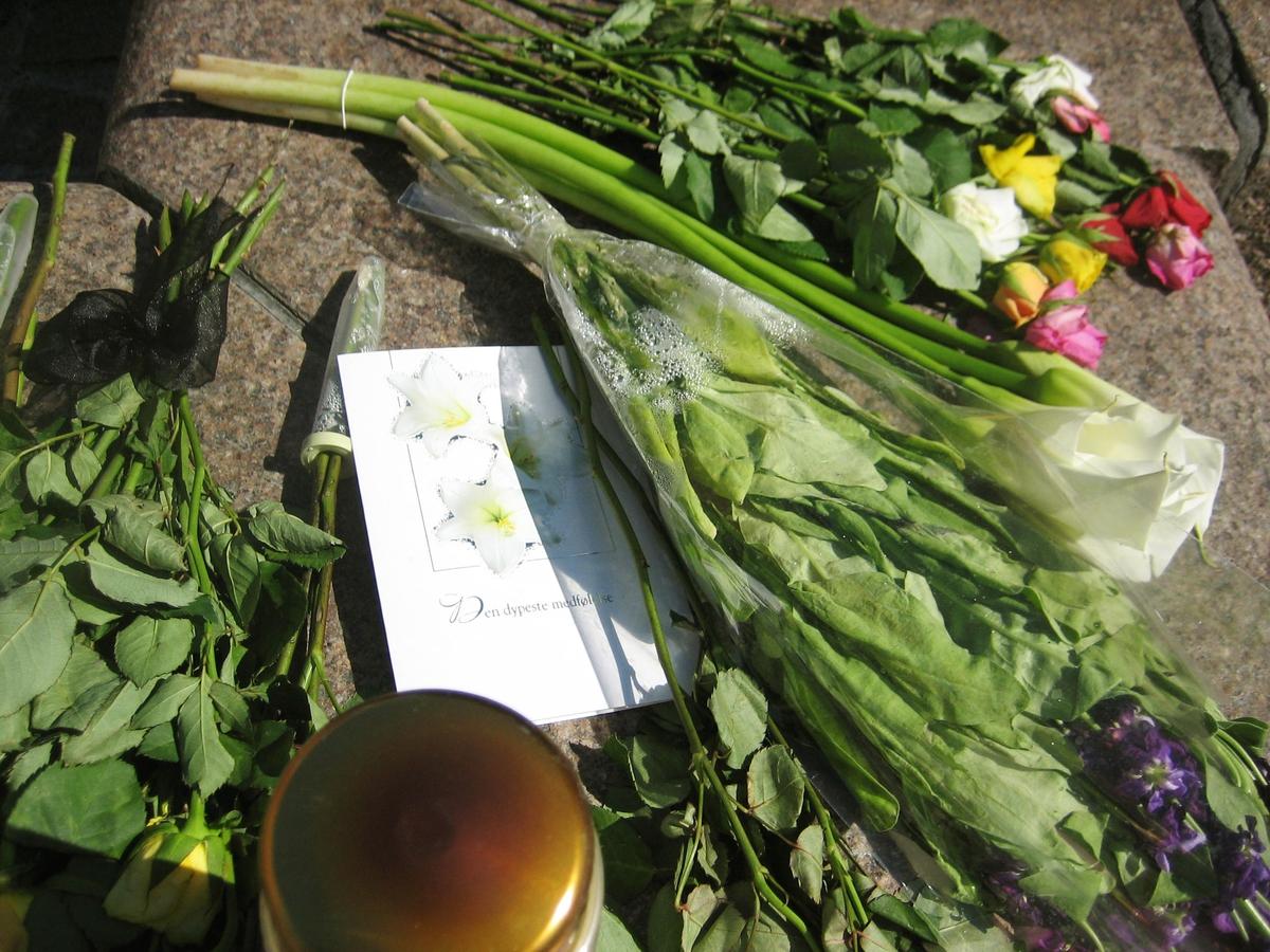 Minner etter terrorhandlingen den 22. juli 2011. Blomster, kort og lykte ved fontene på Lillestrøm torg.