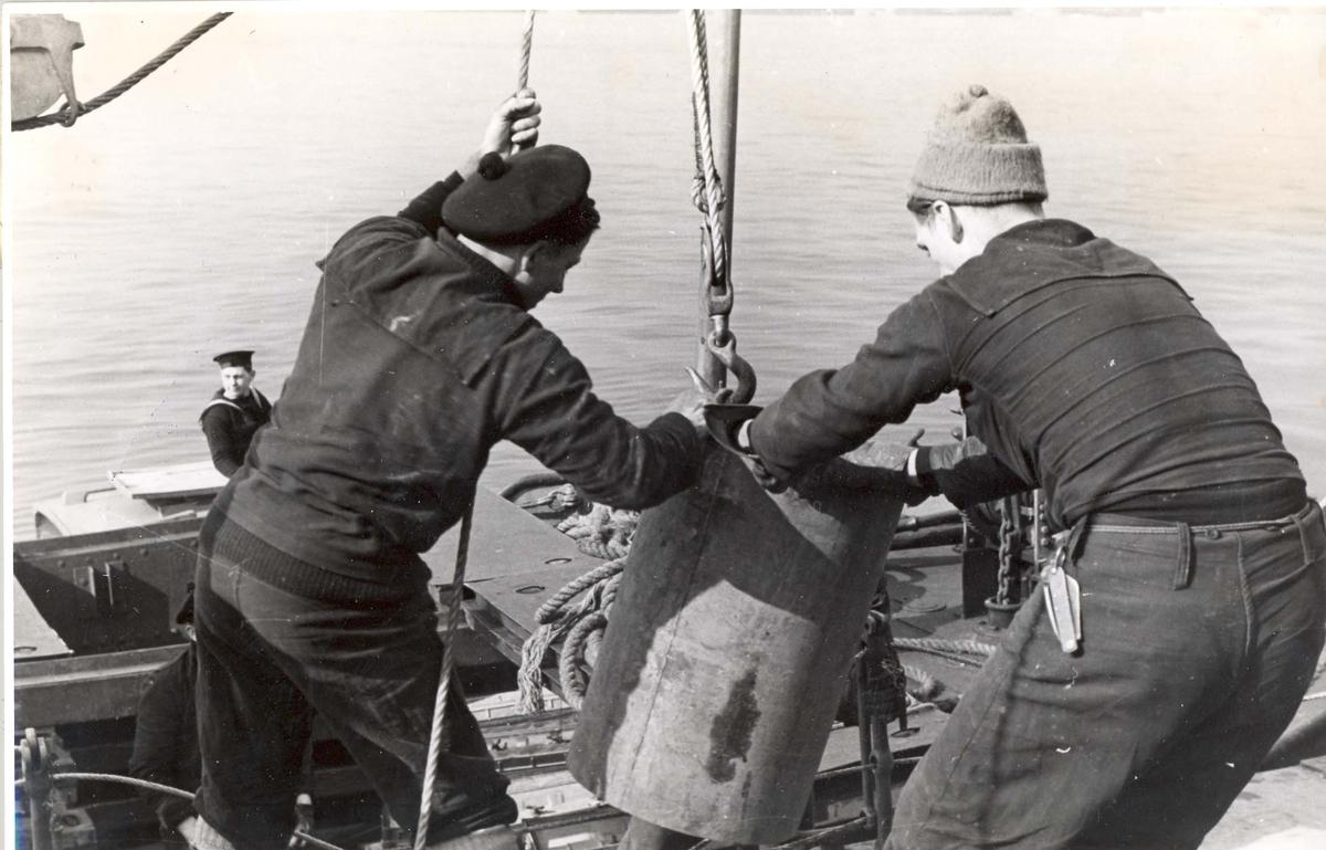 """Enkeltbilde. Jageren """"Stord"""" under oppøving, klarsjøing. Dypvannsmine blir heist ombord på skipet under oppholdet i Scapa Flow"""