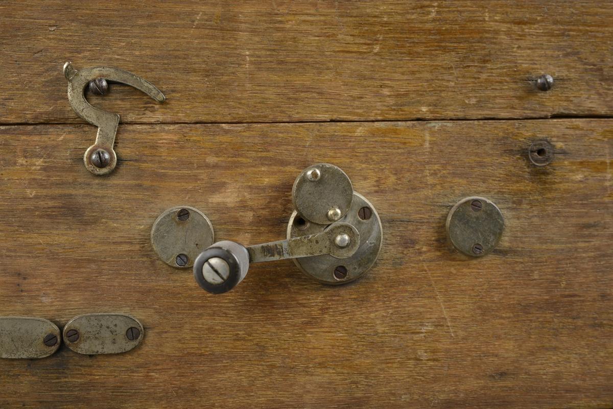 Telefon med treeske. Kassen har et hengslet lokk med kroklåser. Håndtakene på kortsidene er av metall og kan slås inn slik at de er jevne med kasseveggen. Et kraftig bærehåndtak av messingfarget metall er festet på lokket. To batteri av Hellesens fabrikat sammen med telefonen i treesken.