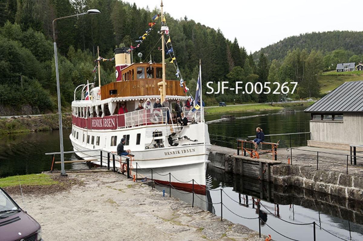 Turistbåten «Henrik Ibsen» på veg mot Kjeldal sluse i Bandak-Norsjø-kanalen på sin rute fra Dalen til Skien.  Sluseanlegget ligger i Nome kommune.  Her er det ett slusekammer, som utlikner en høydeforskjell på tre meter mellom ovenforliggende og nedenforliggende del av vassdraget.  Henrik Ibsen er det største, raskeste og mest luksuriøse skipet i Skiensvassdraget.  Fartøyet er opprinnelig bygd som dampskip ved Eriksbergs Mekaniska Verkstad i Gøteborg i 1907 for Styrsö-bolaget.  Derfor fikk båten først navnet «DS Styrsö».  Under dette navnet gikk fartøyet i mange år som rutebåt i Gøteborg-skjærgården.  Etter en periode som charterbåt på den svenske vestkysten ble Styrsö oppkjøpt av Skien Dalen Skipsselskap AS og satt trafikk i Skiensvassdraget i forbindelse med Bandak-Norsjø-kanalens 100-årsjubileum i 1992.  Her fikk båten navnet «MS Henrik Ibsen», etter den berømte forfatteren med tilknytning til Skien og en hurtiggående dampbåt som gikk i vassdraget tidig på 1900-tallet.  I perioden 2009-2011 ble skipet restaurert med sikte på at det igjen skulle framstå som det hadde gjort da det var nytt.  Etter dette har fartøyet vært driftet av Norwegian Hospitality Group AS, som eier Telemarkskanalen Skipsselskap AS.  Selskapet disponerer også det tradisjonsrike drakestilhotellet på Dalen, som er endestasjon for båtruta.  Sesongen for kanalbåtene starter vanligvis i midten av mai og varte til andre halvdel av september. Seilasen mellom Skien og Dalen med turistbåten Henrik Ibsen tar cirka ni timer. MS Henrik Ibsen har aller rettigheter og det er restaurant ombord med daglig servering av frokost og lunsjretter.  Båten går opp den ene dagen og ned igjen den neste.  Turistbåten MS Victoria går ned til Skien den dagen Henrik Ibsen setter kurs for Dalen, og går ned igjen den dagen den andre båten er på veg opp.