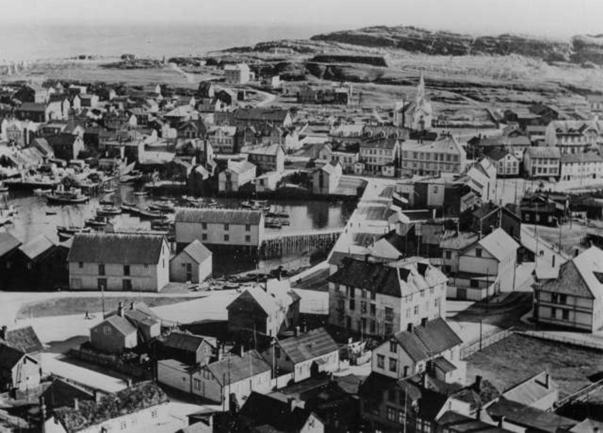 Flofoto. Utsikt over Vardø før byen ble ødelagt i oktober 1944. Tehusbebyggelse, havn og i bakgrunnen sees Vardø kirke.