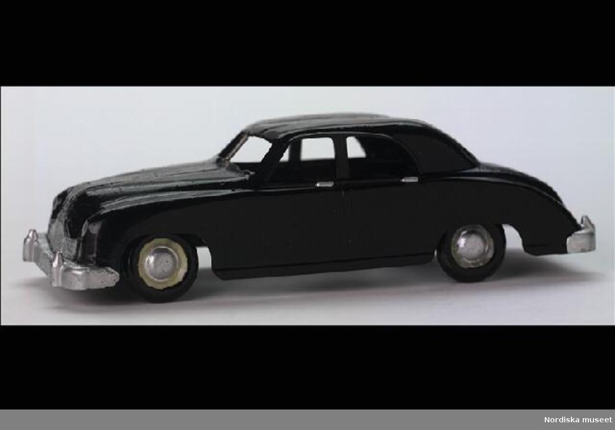 """Inventering Sesam 1996-1999: L 12,8,B 4,7,H 3,7cm Bil av märket Kaiser, svart plast, delvis hembygge. Silverfärgsmålade detaljer, öppna fönster, ingen inredning eller underrede. Svarta däck av plast med detaljer i gulvitt och silver. Gjuten märkning undertill: """"SEMO/MADE IN SWEDEN"""". Enligt bilaga inköpt 8/1 1951 av givaren för 1,50 hos F G Anderssons Eftr., Strängnäs. Givaren samlare av leksaksbilar 1947-1952, de inv.nr. 263.905 - 264.120. Bilaga Helena Carlsson 1996"""