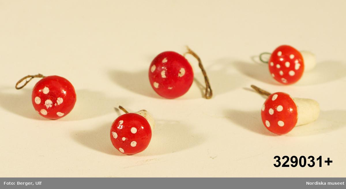 """Flugsvamp av papier maché, 5 st. Röd rund hatt, vita prickar, vit fot, grön papperslindad metalltråd utstickande från foten.  Ingår  i tomtelandskap inv.nr 329001-329034. /2006-09-01 Heidi Henriksson och Lena Kättström Höök    Tomtelandskap har funnits i borgerliga familjer åtminstone från 1920-talet och framåt. Förutom benämningen """"tomtelandskap"""" kan det t ex också kallas """"julbord"""" eller """"vinterlandskap"""". Kyrkan intog en  central plats i landskapet och olika scenerier och aktiviteter utspelade sig alltefter den skapande familjens fantasi och smak. Detta tomtelandskap skapades av givarinnans mormor Frida Pettersson (1878-1963) på 1920-talet i Norrköping. När givarinnans mor Dagmar, (1910-2001) gifte sig 1937 med P W Ennerfelt ( f. 1905) flyttade hon till en lägenhet i området Kneipen i Norrköping och fick med sig tomtelandskapet. I familjen föddes barnen Göran 1940, Claes 1942 och Ingrid 1951. Familjen flyttade småningom till villa med trädgård i samma stadsdel Kneipen på Lokegatan 18. Här finns kyrka i skånsk stil belyst inifrån med batterilampa. Vid kyrkporten en präst. Runt en julgran dansar ett antal garntomtar, andra tomtar rider på julbock, åker skidor, någon hugger ved mm. Vid ett härbre dras  en vedkälke av ett rådjur, vid brunnen vevar en tomte upp vatten och tomtemor kokar gröt i en kopparkittel medan katten tittar på. Typiskt för dessa landskap är att man förändrar och lägger till alltefter tidens gång och att man tillverkar prydnader själv och köper in nya figurer. Under 1970-talet lekte givarens brorssöner med bilar och då var en del av dem utplacerade i jullandskapet . En av pojkarna spelade tennis varför en av tomtarna hade en tennisracket i handen(bilar och racket ingår ej i den erbjudna gåvan). Tidigare fanns  också en spegelbit invid en vedstock (finns fortfarande) föreställande en isbelagd sjö och på den en skridskoåkande tomte och vid stranden en båt. Tomtelandskapets brunn tillkom på 1950-talet. mamman sydde ett förklä till tomten. besökare kmme"""