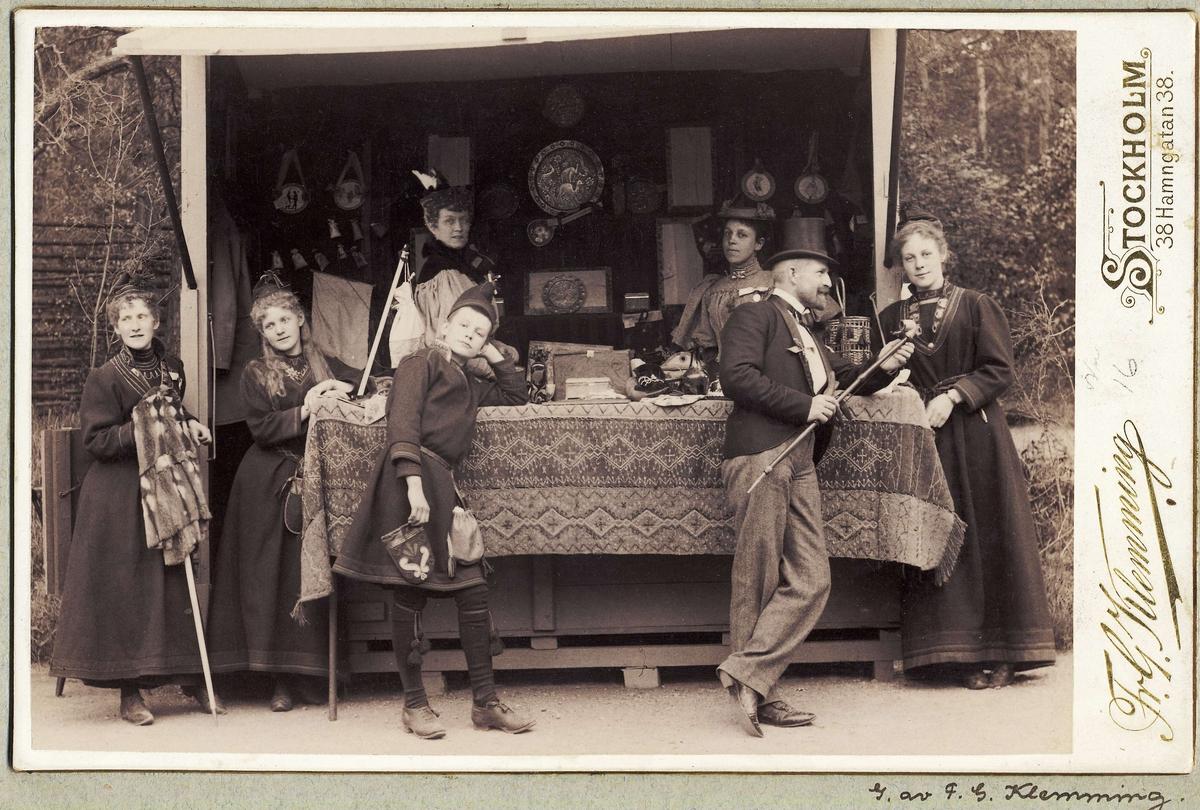 Skansens vårfest 1895. Herre i cylinderhatt och kavaj, kvinnor och pojke i samiska kläder vid bod med samehantverk