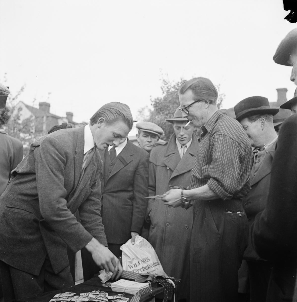 """Höstmarknad på Vaksala torg, Uppsala 1948. Bertil Odin """"demonsterar hur man behändigt knyter sin slips med hjälp av en ståltrådsställning""""."""