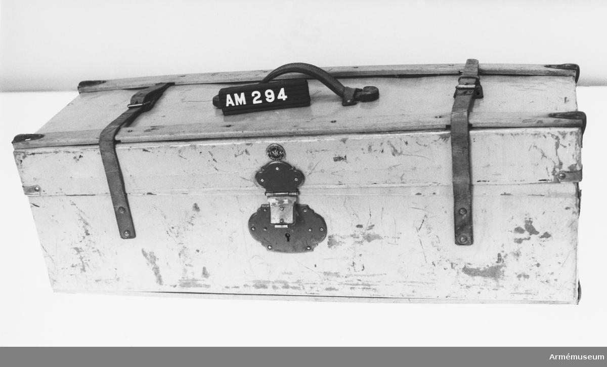 """Samhörande nr är 229-233, 294-299, 321-350, 400-448. Packlåda m/1915, serg (uoff). Gråmålad """"unica""""-packlåda, förstärkt på locket och i botten med 35 mm breda träribbor, fastnitade på fyra ställen och i hörnen svarta järnbeslag. Mitt på locket ett kraftigt bärhandtag i läder. Spännremmar, fastsatta på sidorna, gående under ribborna och med spännet mitt på locket 140 mm från sidorna. Rödlackerat metallås monterat mitt på lådans framsida, 35 mm från överkant. Låsbart. Märkt: Aktiebolaget.Tidan.Mariestad.Unica. Står i guldtryck på svart botten på ett runt märke, diameter 25 mm, strax över låsdelen på locket. Medföres på trossen."""