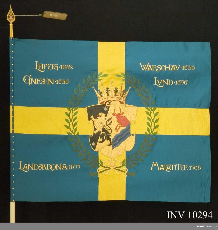 Grupp B I.  Fana m/1899 för infanteriet, Skaraborgs regemente III. Från Arméförvaltningens intendenturavdelning, Modellkammaren. Modellfana ej utdelad. Enligt Go 649 18990601. Samhörande spets med Oscar II:s namnchiffer som förvaras i rullen.Sidenfana i blå botten med gult kors med målat motiv och segernamn, rakt ställda i de blå fälten. Vapenskölden är omgiven av en lagerkrans och krönt av hertigkrona.