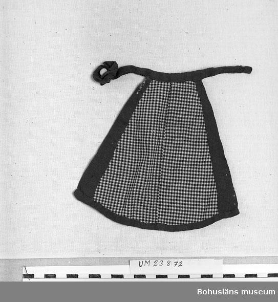 Brunrutigt förkläde, kantat med lila kantband med lila midjeband, allt i bomull. Hör till dockan Adéle, UM023864:001. Slitageskaodor på den lila kanten.  Personuppgifter; se UM0023863.