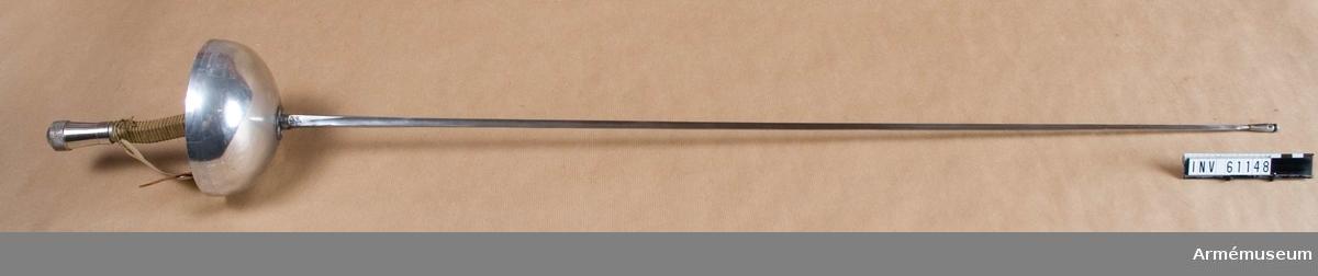 Grupp D III. Tävlingsvärja av franskt fabrikat, Souzy, Paris, monterad i Stockholm 1965. Med anordning för elektrisk markering av stötar. El Point d'arrét med 8 mm platta och 4 mm klingspetsgänga. Bärfjädertrycket överstiger 750 g. Elspetsens totala slaglängd 1,5 mm. Parerplåten av aluminium och decentererad 35 mm. Kaveln lindad med linnetråd och avsedd endast för höger hand.