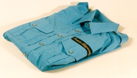 """Uniformsskjorta i blått med mörkblått textilband med text iguldbokstäver:""""Postens diligenstrafik"""" placerat ovanför vänstrabröstfickan. Skjortan har två med klaff försedda bröstfickor ochaxelklaffar."""