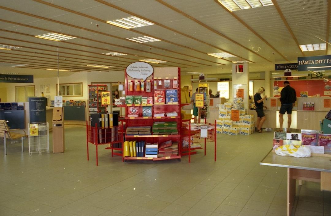 Allmänhetens avdelning på regionpostkontoret Kungshörnet i Uppsala, 1996. I öppna säljmontrar på golvet utbjuds kuvert, paketkartonger och kontorsmaterial mm.