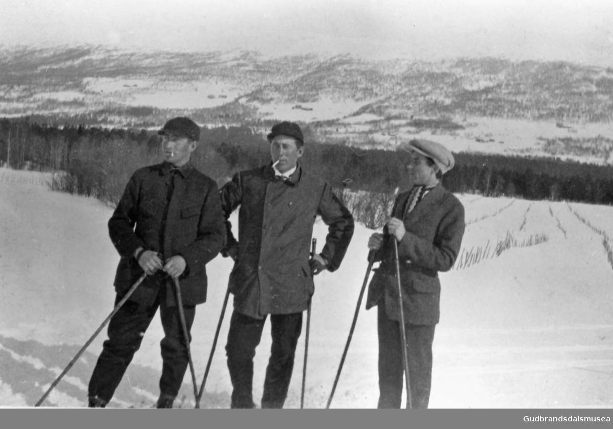 Tre menn ute på skitur ein fin vinterdag, skog og fjell i bakgrunnen.