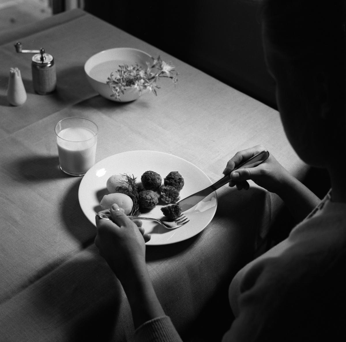 Servus bestick Kvinna som äter köttbullar och potatis. C.-H. Stålhanes servis från Rörstrand och Servus bestick av Sigurd Persson från Kooperativa Förbundet