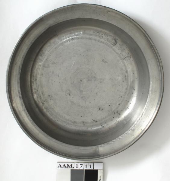 Stående kvinneskikkelse i gevant  holder et skipsanker  i den ene hånd, mens den annen støtter et ovalt skjold.