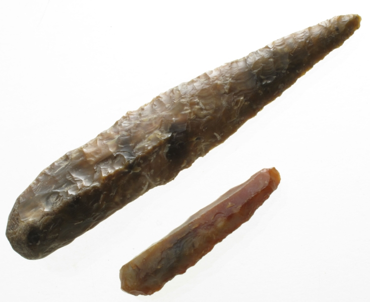 Dolk av brunlig, spettet flint, av typen [Rygh fig.63] R. 63. Kalkskorpen sitter igjen i enden av grepet. Bladet sterkt oppskjerpet, ellers godt bevart.