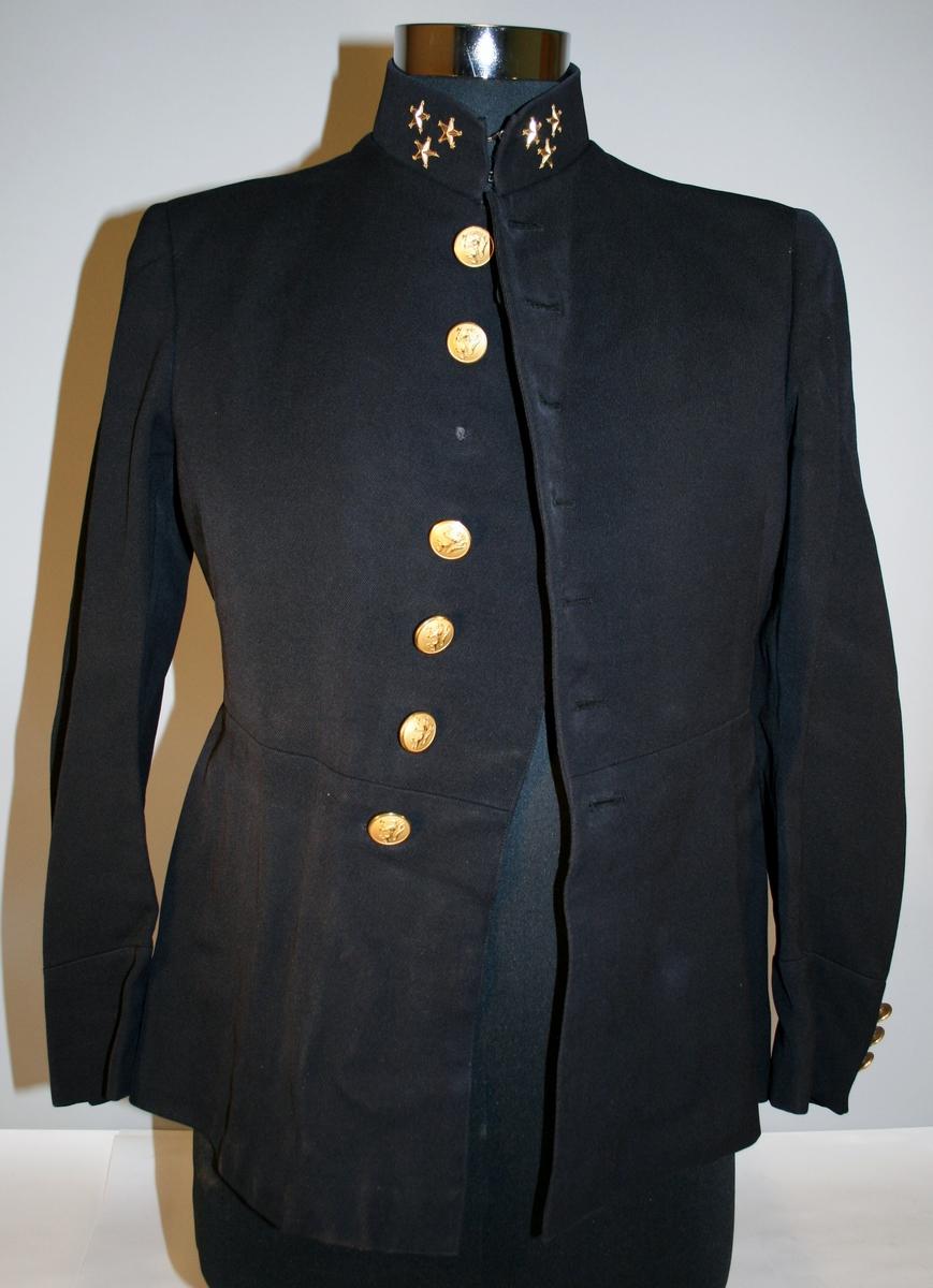Sort uniformsjakke med tre gullstjerner på kragen. Enkeltspent med sju knapper. Tre knapper på hvert erme. Seks knapper bak, tre på hver side av splitten. Alle knapper er forgylte. To brystlommer på innsiden. Ingen lommer på utsiden.