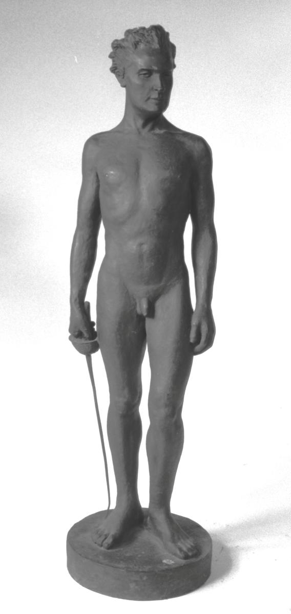 Mann, akt, stående, høyre  ben frem, kårde i venstre hånd, ansiktet høyrevendt.