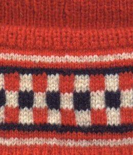 Mössa i 3-trådigt rött ullgarn. Mössan är resårstickad med en slätstickad vit och blå ,rutmönstrad bård på uppslaget. På toppen en isydd tofs.