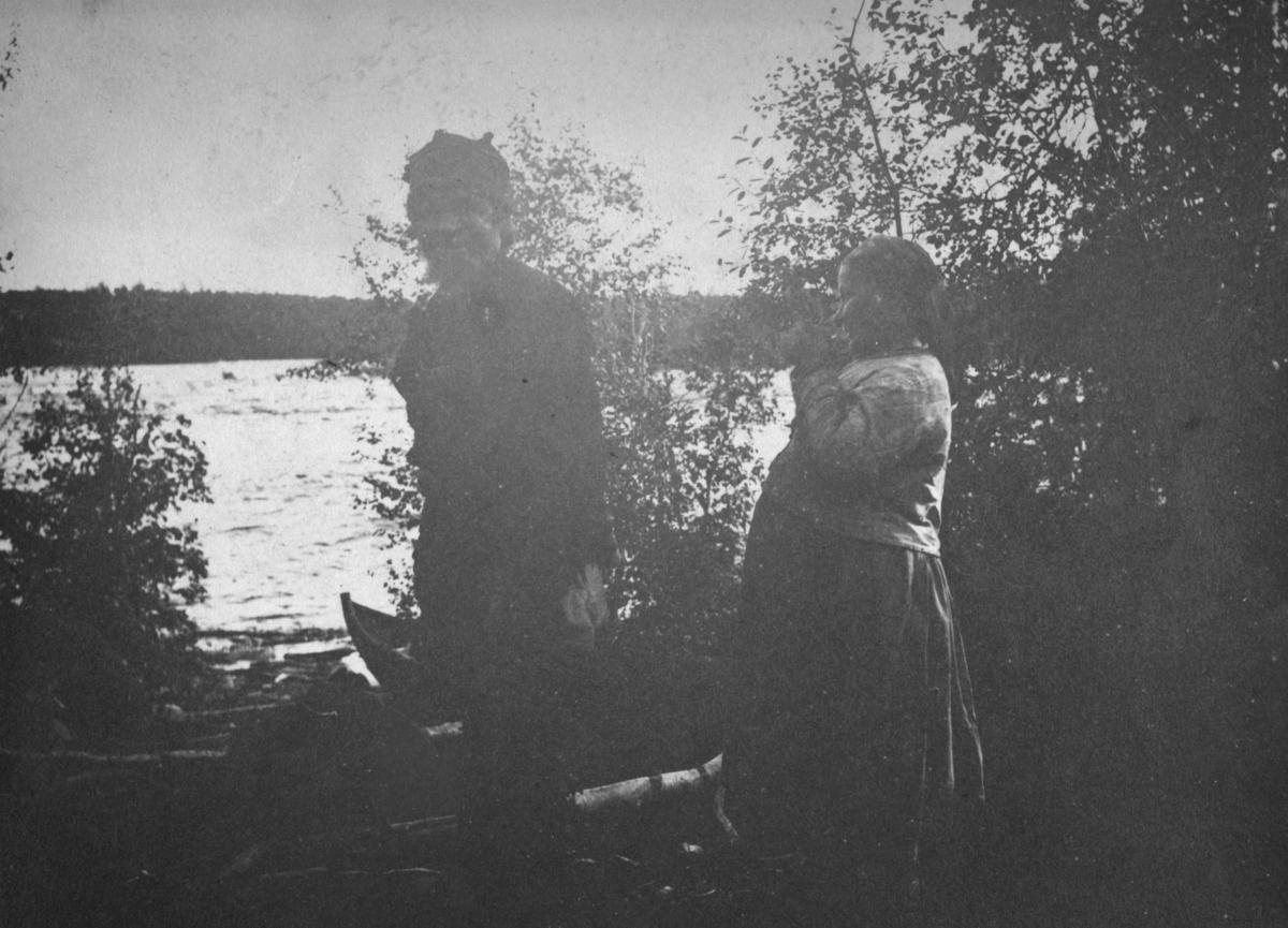 En mann og en kvinne ved en elv. Kvinnen ser ut til å være gravid.