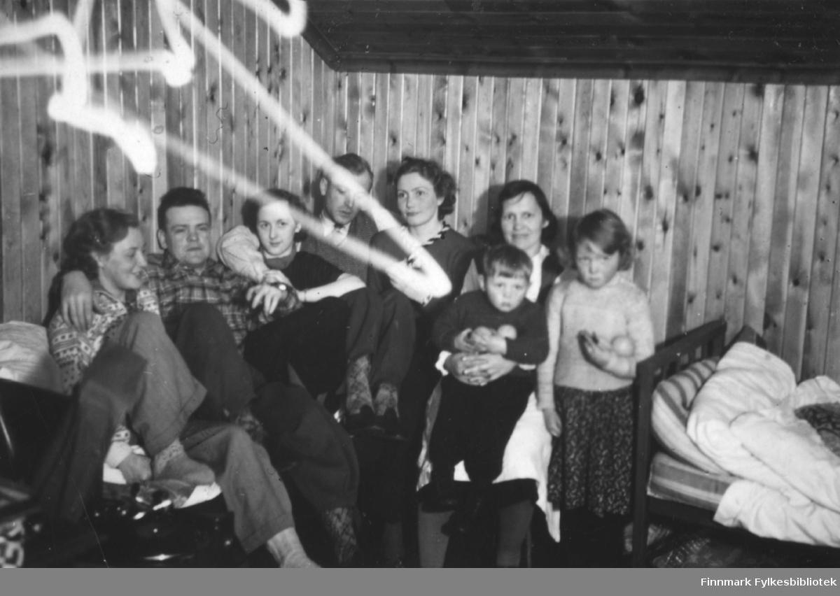 Fra et rom på Neiden fjellstue. Til høyre i bildet sitter oppsitteren på fjellstua, Marie Sivertsen, med sønnen Andreas på fanget og datteren Erna stående ved siden av