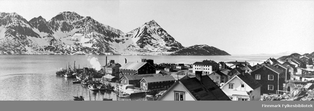 Et oversiktsbilde fra Øksfjord sentrum. Det ligger enda noen snøklatter i fjellene på andre siden av fjorden, så dette bildet er nok tatt om våren. Vi ser toppen av noen hus i forgrunnen og ned mot kaien og pakkhusene. Ved kaien ligger det mange båter, frå et av pakkhusene kommer det damp, forts... kommer det damp, finskeindustri? Ellers gir dette bilde et et godt overblikk over sentrum rundt 1950.