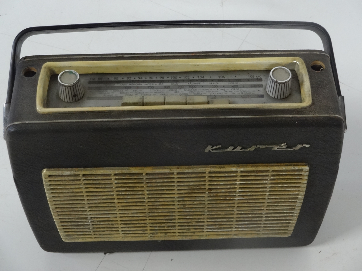 """Transistorradioapparat fra Radionette av type Kurér med tilleggsbetegnelsen """"Marine deluxe"""".   Radioen har merker på undersiden som forteller at den kostet 590 kr og hade en stempelavgift på 47,50 kr. Apparatet fungerer ikke.  Det er og mulig å koble til båndspiller / grammofon.  Batteri er borte."""