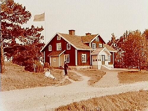En och en halvvånings bostadshus med frontespis, glasad förstubro och förstuga.2 personer framför huset.Johan Karlsson