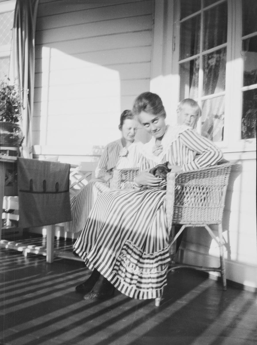 Fra venstre: en uidentifisert kvinne, Ise (Louise) Mathiesen med en liten dachs på fanget og broren Iacob bak, sitter på veranden.