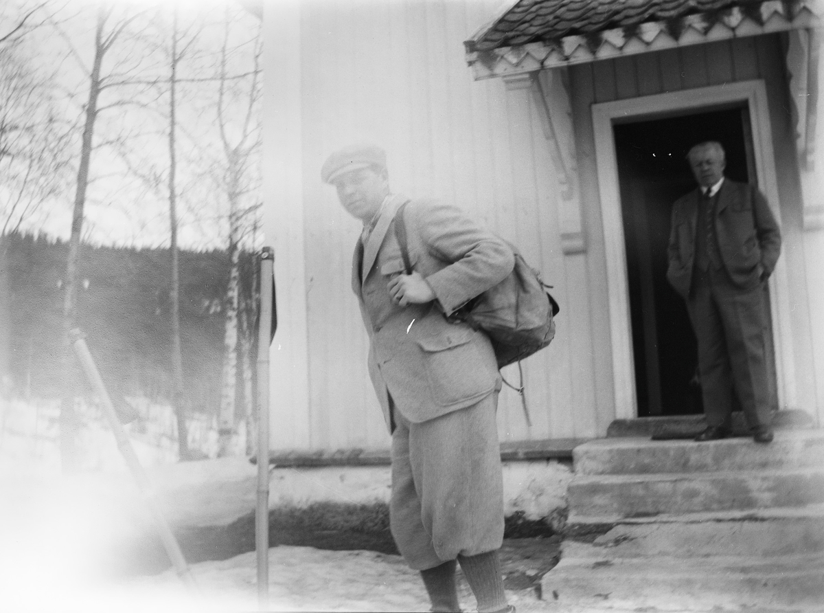 Christian Pierre Mathiesen står på trappen til et hus foran en åpen dør og ser mot fotografen. Carl med ryggsekk og kledd i sportsklær.