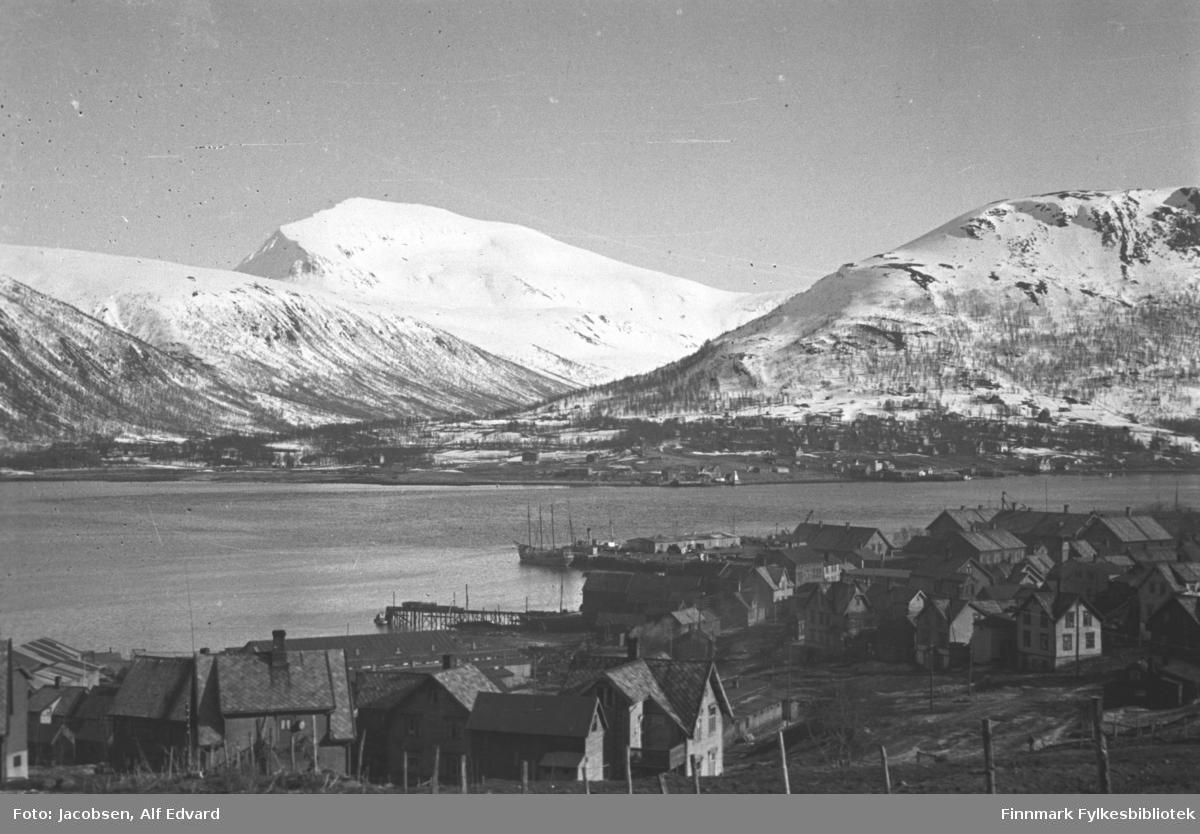 Tromsø fotografert like etter krigen. Nærmest kamera er bebyggelsen på Tromsøya. Husene ligger ganske tett og nede mot sjøen ligger flere større bygg, antagelig havnebygninger/forretninger. Husene har forskjellig størrelse, form og farge, men mange av dem har skiferdekke på taket. Nederst på bildet står gjerdestolper med netting i mellom. Nederst på øya står en trekai som går et stykke ut i sjøen. Litt til høyre for den ligger en annen kai med en lang og lav havnebygning. To båter ligger ved den kaia. Sjøen midt på bildet er Tromsøysundet. Fjellet til høyre er Fløya. I midten ligger Blåfjellet og ved siden av det er enden av Rundfjellet. Dalen midt på bildet er Tromsdalen. En del snø ligger i fjellet og ganske mye trær vokser i fjellsidene. En del bebyggelse står i strandkanten på fastlandssiden på høyre side av Tromsdalen. Litt vinddrag ses på sjøen, men blå himmel gjør det til en værmessig fin etterkrigsdag.
