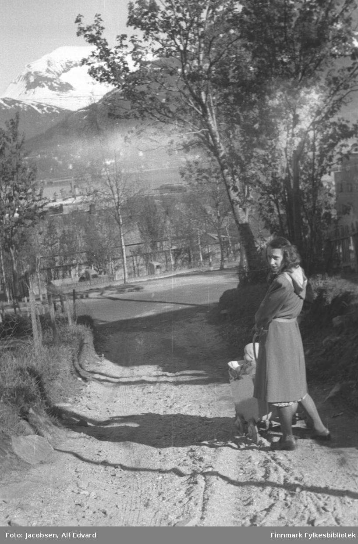 Aase Jacobsen triller sønnen Arne Jacobsen i barnevogn. Hun har en ganske lys kåpe med hette, og lyse sko på seg. Nederst ses kanten på en mønstret, lys kjole under kåpa. Den lyse barevogna er delvis skjult bak henne, men de småe hjulene med store hjulkapsler ses ganske dypt nede i grusen/sanden og kalesjen er nedslått. Litt av Arne ses sittende med lys topplue og jakke i vogna med en stor pute foran seg. Veien de er på er grusdekt og smal. Ganske høye gressdekte kanter er på begge sidene av veien. Til venstre på bildet ses et nettinggjerde med tynne stolper. På høyre side står flere store løvtrær og et stakittgjerde. I enden av veien går en bredere gate på tvers og flere løvtrær står i veikanten der også. Like nedenfor veikanten ses førerhuset og litt av karmene på to lastebiler. Helt til høyre på bildet ses hjørnet på et stort bygg. I enden av området ses deler av Tromsø by på Tromsøya. Sjøen som ses ganske langt oppe på bildet er Tromsøysundet. På andre siden er fastlandet med Tromsdalen. En del snø ligger enda på toppen av Nordfjellet så bildet er nok tatt ganske tidlig på sommeren.