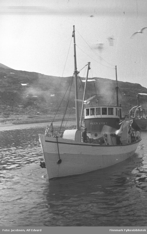 Televerkets båt M/K Peer Gynt på havna i Havøysund. Båten har en skrog som er malt i en lys farge med en hvit stripe oppe mot rekka. Øverste og nederste del av styrhuset er hvitt og ganske tett med vinduer. Mellom de delene er et område med trefarget panel og navnet på båten. I baugen henger dreggen og i fra hullet på babord er kjettingen. Foran står en høy mast med bom. Tauverk går fra masten og mot baugen og rekka. Mellom masta og baugen er nedgangen til lugaren. En mann i mørke klær står på dekk. På babord side av styrhuset er stativ der livbåten henger. Nærmere hekken står en aktermasta som er noe lavere enn masta foran. På andre siden av havna ligger et fjell. Jordet til venstre på bildet er Klokkarjordet. Noen få snøflekker ligger i fjellet. Øverst til høyre på bildet flyr en måke. Sjøen er blikkstille og klar himmel tyder på en værmessig flott vår-/sommerdag.