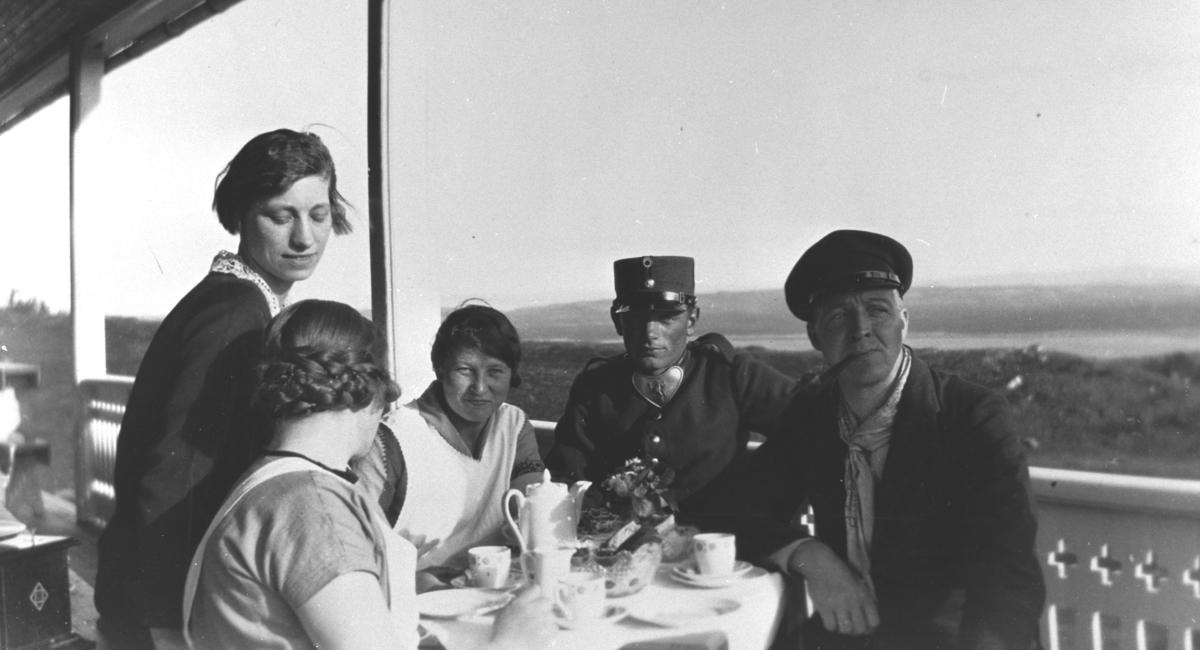 Bestyrer Olav Korsvik og tre av betjeningen av soldaterhjemmet  i Nyborgmoen fotografert på verandan sommeren 1927. To av kvinnene og bestyreren sitter ved kaffebord som er dekket med et hvit duk, porselenkopper, blomster og en kaffekanne.   Soldaten som sitter ved bordet er ukjent, vi vet heller ikke navnet til de tre kvinnene som jobbet i soldaterhjemmet.