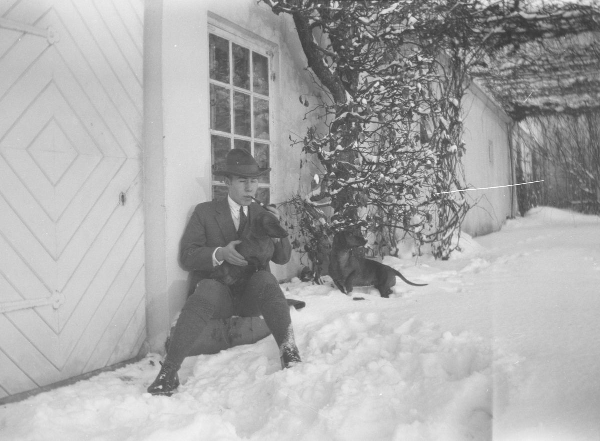 Iacob Ihlen Mathiesen sitter, på en stein eller lignende, utenfor en dør i grunnmuren til hovedhuset på Linderud Gård, med ham to dachser.