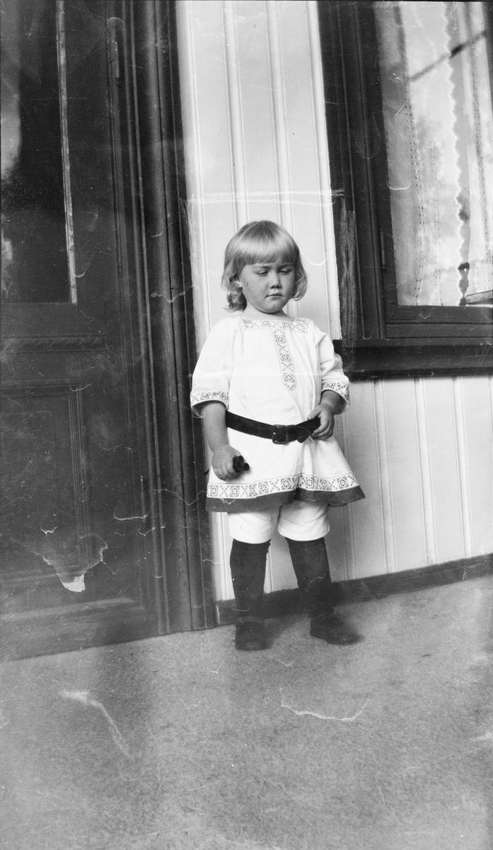 Iacob Ihlen Mathiesen står ved en husvegg, mellom en dør og et vindu med blondegardiner. Det må være på en veranda eller et inngangsparti siden han står på et gulv. Han er kledd i tunika med belte i livet og kortbukser.
